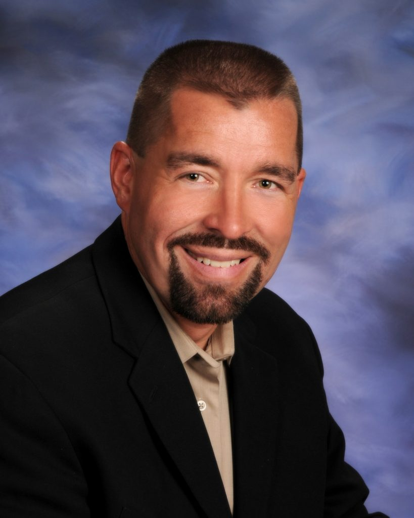 head shot of man with goatee smiling