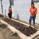 Two students digging in the garden bed.