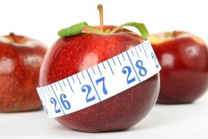 red apple with white measuring tape