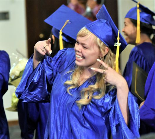 oic graduate holding up two peace sign